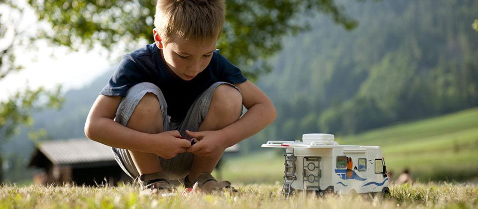 Un bimbo che gioca con un camper giocattolo nelle montagne dell'Alto Adige
