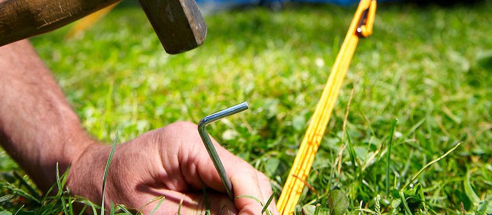 Un picchetto per la tenda viene piantato in un verdissimo prato